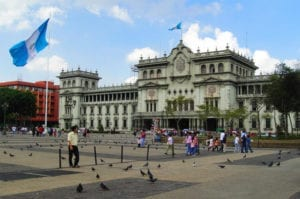People walking among pigeons in front of the National Palace of Culture in Guatemala City
