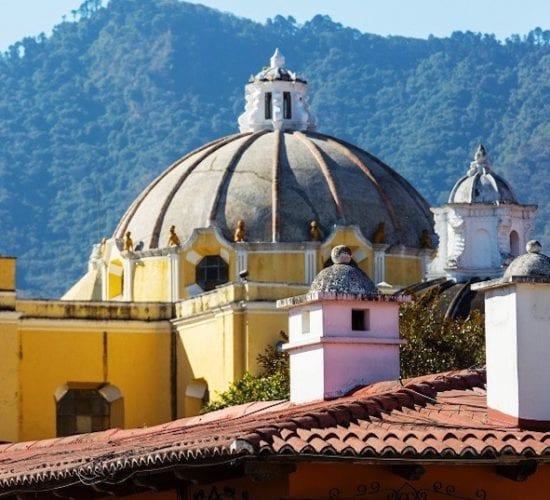 Church roof in Antigua Guatemala with mountains in the background. Guatemala Family Vacation Package