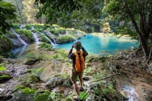 Man taking photos in the natural pools of Semuc Champey, Guatemala. Central America Tours