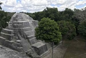 View of a temple in the Mayan City of Yaxha surrounded by jungle. Guatemala tours
