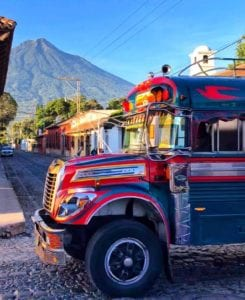 Public bus passing by on a Antigua Guatemala street with the volcano de Agua as background. They are colloquially known as Chichen Buses. Coronavirus Travel Guidelines