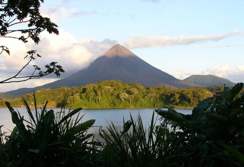 Perfect conic form of Arenal volcano across the lagoon in a Costa Rica vacation