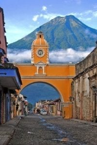 Arch street and volcano on the background in a Guatemala tour. Coronavirus Travel Guidelines